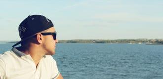 Человек в крышке смотрит на море Стоковое Изображение