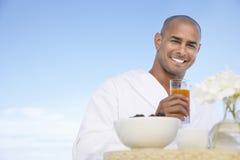 Человек в купальном халате держа стекло сока стоковое изображение