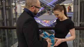 Человек в куртке дает подарок к молодой женщине и она обнимает его в магазине крытом Она усмедется видеоматериал