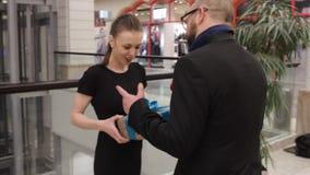 Человек в куртке дает подарок к молодой женщине и она обнимает его в магазине крытом Она усмедется акции видеоматериалы