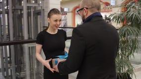 Человек в куртке дает подарок к молодой женщине и она обнимает его в магазине крытом Она усмедется сток-видео