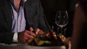Человек в куртке, фиолетовой рубашке сидя на таблице в ресторане с женщиной романтично сток-видео
