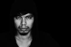 Человек в клобуке с страшной стороной в темноте Стоковая Фотография