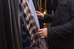 Человек в магазине выбирая рубашку от других одних Стоковые Изображения