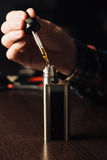 Человек в магазине vape заполняет специальную жидкость в e-сигарете Стоковые Фото