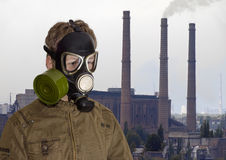 Человек в маске противогаза против фона промышленного ландшафта Стоковые Фото