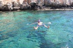 Человек в маске плавает около пещер моря стоковые фото