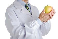 Человек в медицинском белом пальто держа желтое яблоко Стоковые Изображения