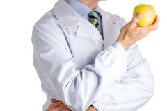 Человек в медицинском белом пальто показывая желтое яблоко Стоковое Фото