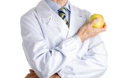 Человек в медицинском белом пальто показывая желтое яблоко Стоковые Изображения