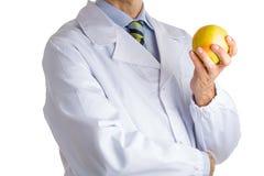 Человек в медицинском белом пальто показывая желтое яблоко Стоковые Изображения RF