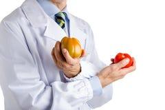 Человек в медицинском белом пальто показывая зеленые и красные зрелые томаты Стоковая Фотография RF