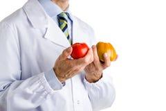 Человек в медицинском белом пальто показывая зеленые и красные зрелые томаты Стоковые Фото