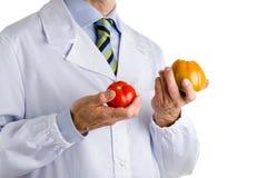 Человек в медицинском белом пальто показывая зеленые и красные зрелые томаты Стоковое Изображение RF