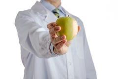 Человек в медицинском белом пальто предлагая желтое яблоко Стоковые Фотографии RF