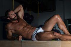 Человек в нижнем белье отдыхая на коробке после тренировки стоковое изображение rf