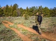 Человек в обмундировании камуфлирования открывая природу в лесе с камерой фото DSLR, объективами, треногой в рюкзаке Путешествия Стоковые Изображения