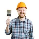 Человек в оранжевом шлеме с щеткой стоковые изображения