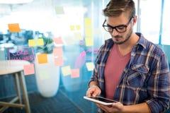 Человек в офисе используя цифровую таблетку против липких примечаний на стене Стоковые Изображения