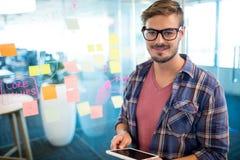 Человек в офисе используя цифровую таблетку против липких примечаний на стене Стоковые Фото