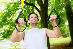 Человек в парке города делая спорт тренера подвеса стоковая фотография rf