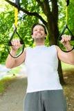 Человек в парке города делая спорт тренера подвеса стоковые фото