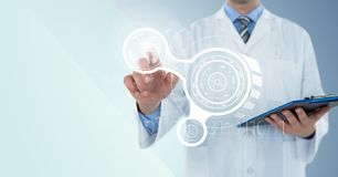 Человек в пальто лаборатории с доской сзажимом для бумаги указывая на белые интерфейс и пирофакел против голубой предпосылки стоковая фотография rf