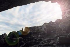 Человек в пещере с предпосылкой неба Стоковая Фотография