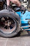 Человек в ремонте автомобиля передвигает с помощью рукоятки используемую покрышку оправы стоковые изображения