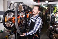 Человек в рисберме рассматривая состав колеса для велосипеда Стоковые Фотографии RF