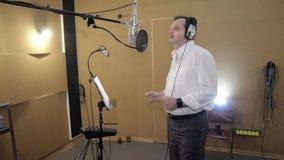 Человек в рубашке поет в наушниках перед микрофоном Пальцы щелчка студия сток-видео