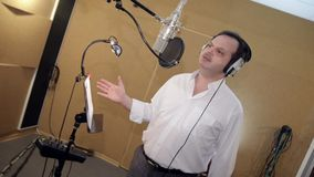 Человек в рубашке поет в наушниках перед микрофоном gesticulation студия сток-видео