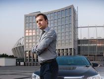 Человек в рубашке представляя около автомобиля Стоковое Фото