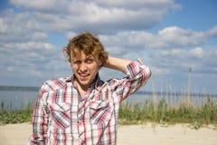 Человек в рубашке шотландки имеет озадаченный взгляд с улыбкой Стоковое Фото