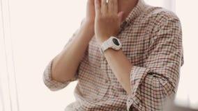 Человек в рубашке шотландки с белым вахтой на руках, сидящ на стуле и жестах, касается стороне, говорит сток-видео