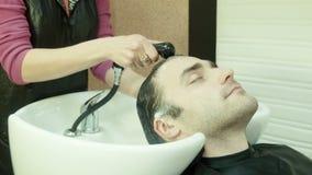 Человек в салоне красоты моет голову видеоматериал