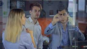 Человек в сером деловом костюме пишет на стеклянной поверхности окна черной отметкой видеоматериал
