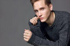 Человек в сером портрете студии свитера стоковые фото