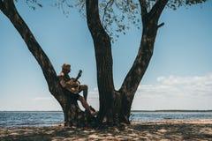 Человек в склонности шляпы на большой гитаре дерева и играть на береге реки Стоковые Изображения