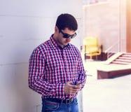Человек в солнечных очках рубашки и джинсов, держа мобильный телефон, прочитал сообщения на вашем, концепцию переговора  Стоковое фото RF