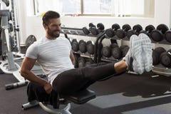 Человек в спортзале, повышении ноги, подбрюшных мышцах Стоковое Изображение