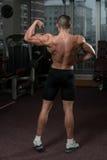 Человек в спортзале показывая его вышколенное тело Стоковые Изображения