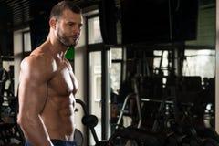 Человек в спортзале показывая его вышколенное тело Стоковые Фотографии RF