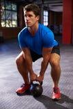 Человек в спортзале работая с весом колокола чайника Стоковое Изображение
