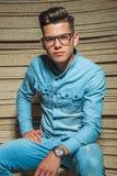 Человек в стеклах джинсовой ткани нося сидя и представляя Стоковая Фотография