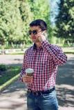 Человек в стеклах рубашки и джинсов, говоря на телефоне, smartphone, концепция лета, каникул бизнесмена стоковое фото rf