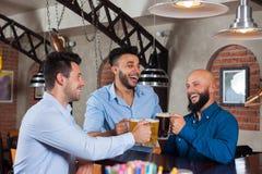 3 человек в стеклах Clink бара провозглашать, выпивая кружки владением пива, рубашки носки друзей гонки смешивания жизнерадостные стоковая фотография