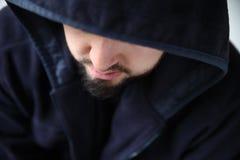 Человек в с капюшоном куртке смотря вниз Стоковые Изображения RF