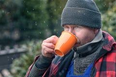 Человек в теплом кофе куртки и beanie выпивая стоковые фотографии rf