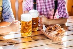 Человек в традиционных баварских одеждах держа кружки пива Стоковые Изображения